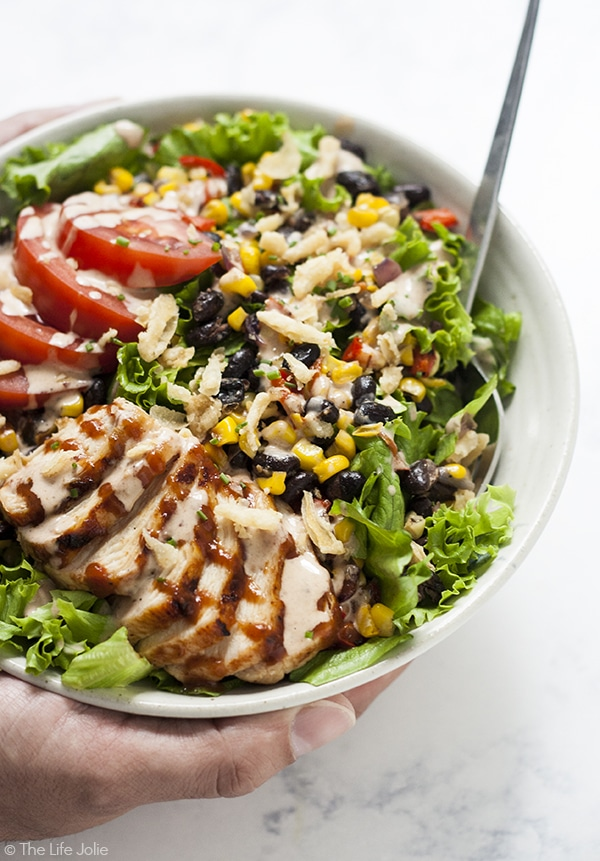 A side angle shot with a man's hands holding a bowl of green salad with BBQ chicken and vegetables on it with a fork sticking out of it.