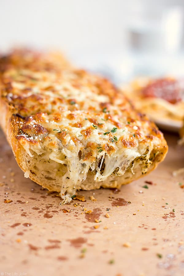 This homemade Three Cheese Garlic Bread recipe is a super easy accompaniment to a delicious Italian meal (or any meal for that matter!). It's really quick to spread with butter, herbs and a ton of melted cheese and pre-cut so that it's even easier to pull apart and enjoy with dinner! This is a major family favorite!