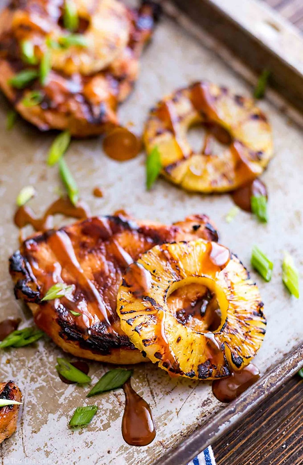 The side of a pan focusing on pork chops and pineapple rings drizzled with Hawaiian BBQ sauce and topped with chopped scallions.