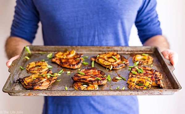 A man in a blue shirt holding a pan of grilled pork chops and pineapple.