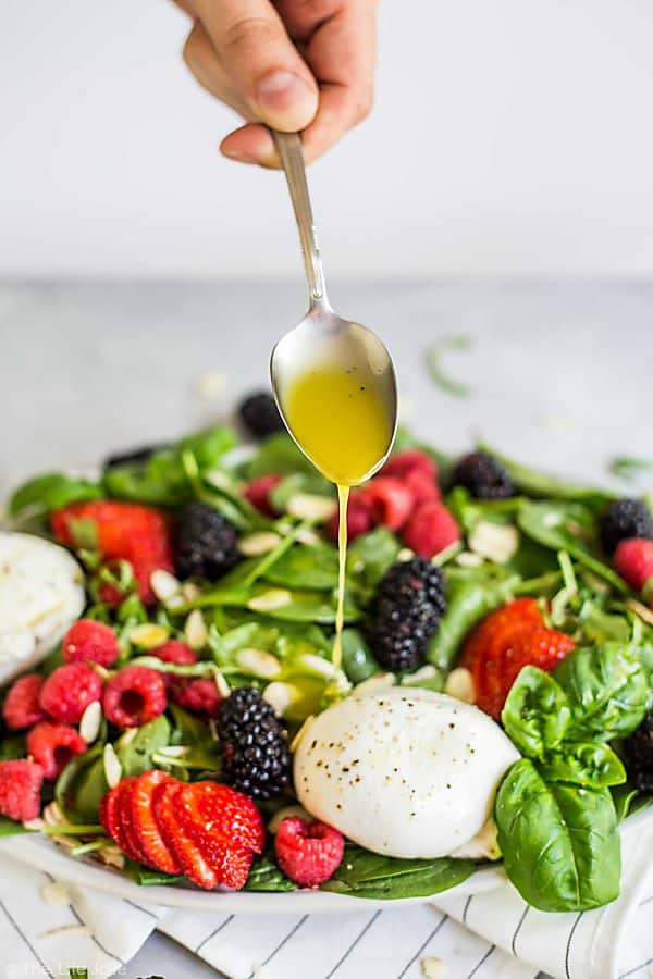 Summer Berry and Burrata Salad with the dressing being drizzled on top.