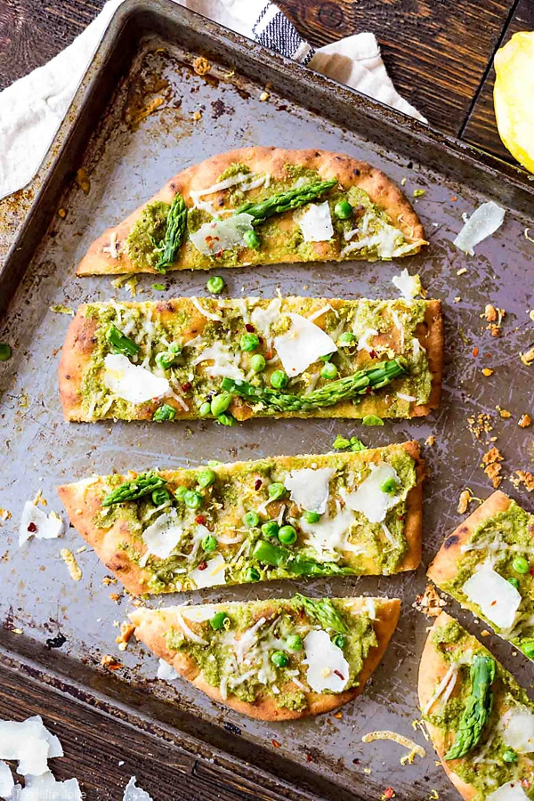 A photo of sliced Pea Pesto Flatbread taken from an overhead angle.