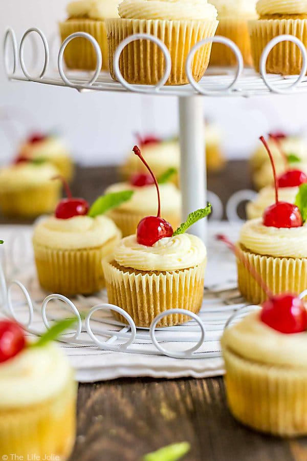 The bottom tier of a cupcake stand with one cupcake in focus and other Mai Tai Cupcakes around it.
