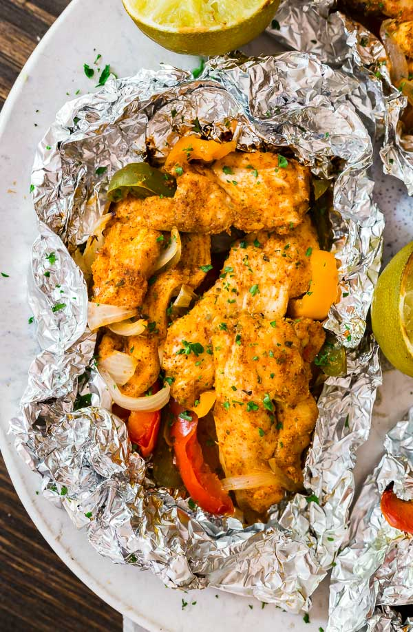 An overhead shot of one Foil Packet Chicken Fajitas packet on a platter with some grilled limes around it.