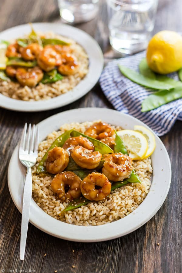 A plate of Shrimp and Snow Peas Stir Fry on brown rice with another plate in the background.