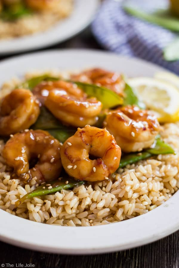 A close up image of Shrimp and Snow Peas Stir Fry on a plate of brown rice with another plate out of focus in the background.
