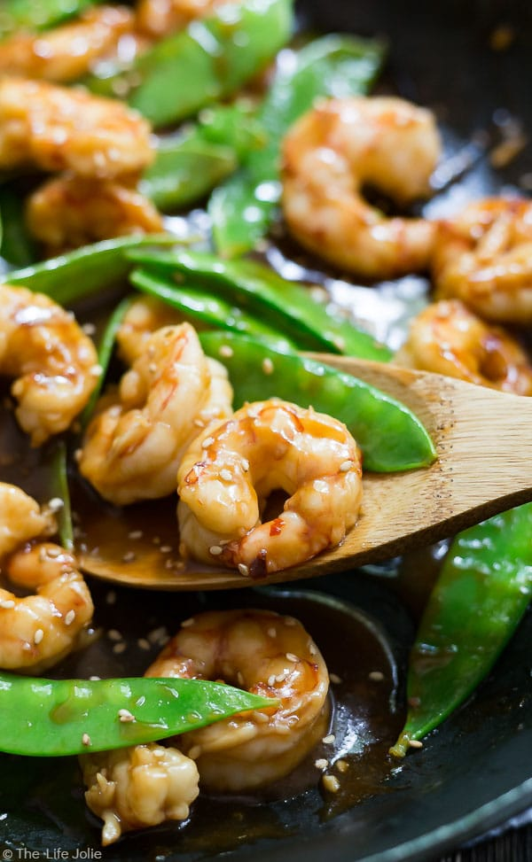 A close up image of Shrimp and Snow Peas Stir Fry in a pan with some shrimp on a wooden spoon in the pan.