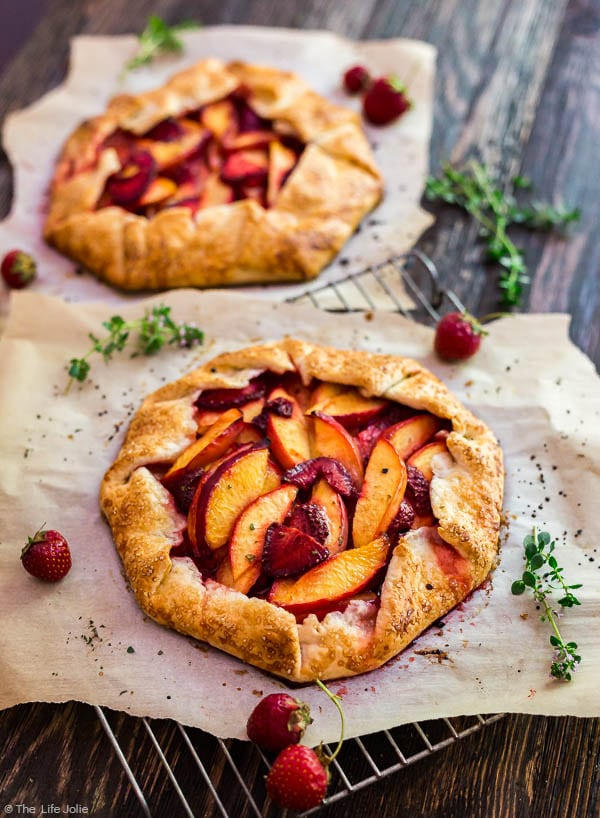 an image of a Nectarine and Strawberry Galette with Thyme on a cooling rack with parchment paper and another galette out of focus behind it.