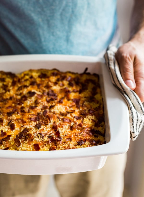 A man's hand holding a pan of Bacon Ranch Creamy Macaroni and Cheese.