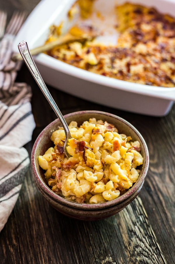 A bowl of Bacon Ranch Creamy Macaroni and Cheese with a spoon sticking out of it.