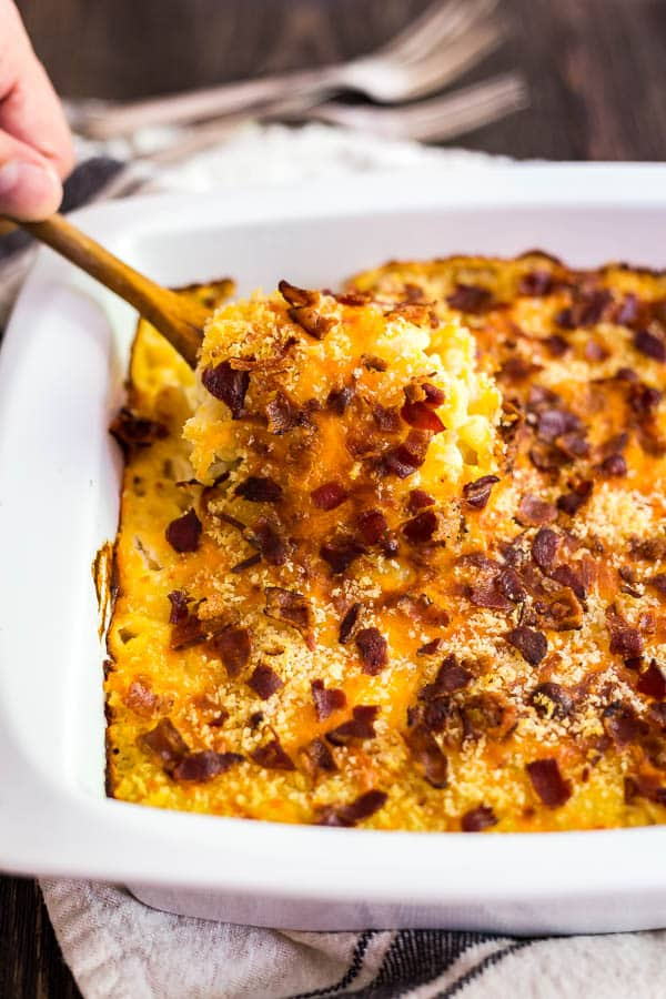 A spoon lifting out of a pan of Bacon Ranch Creamy Macaroni and Cheese.