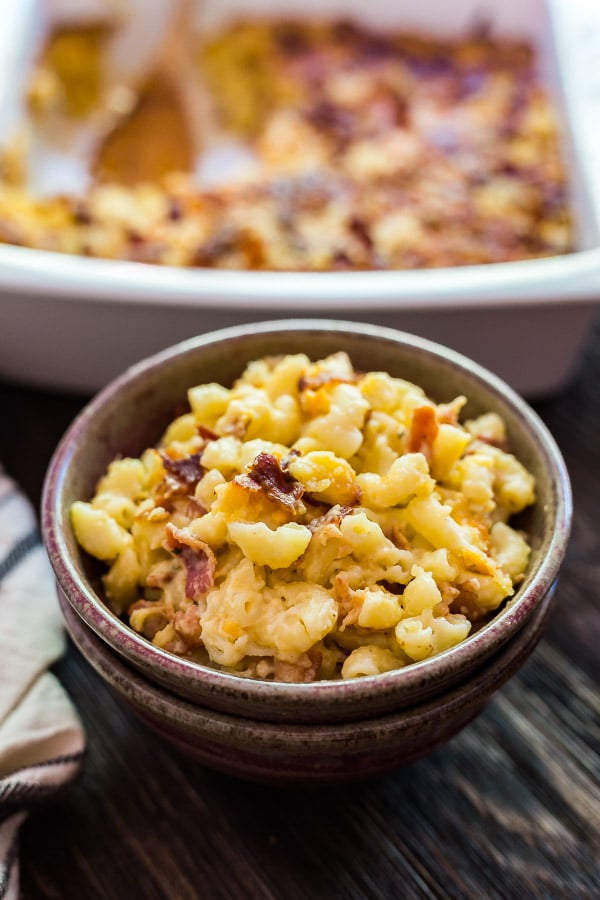 A bowl of Bacon Ranch Creamy Macaroni and Cheese with a pan of it in the background out of focus.