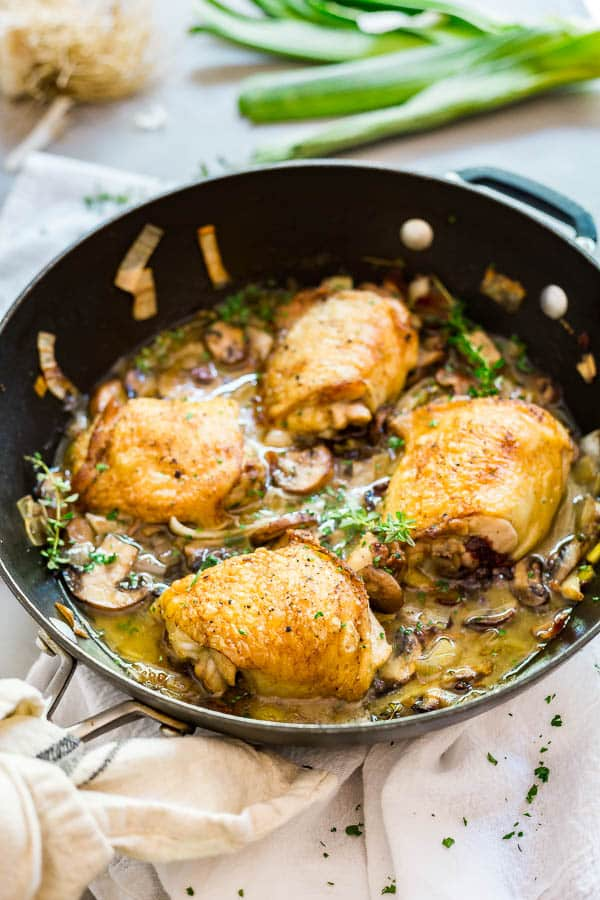 A pan of Champagne Braised Chicken Thighs on white cloth.