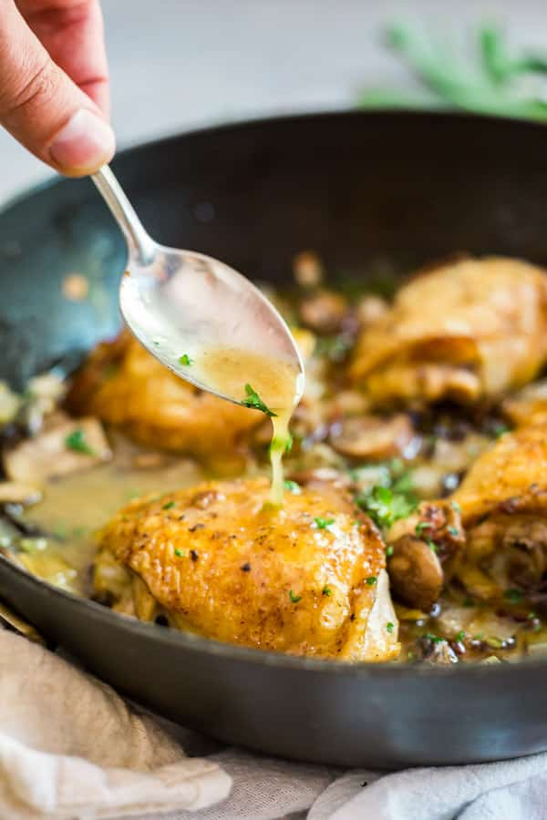 Champagne Braised Chicken Thighs in a pan with a spoon pouring liquid on on of them.