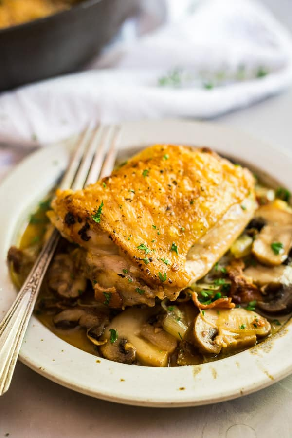 Champagne Braised Chicken Thighs in a plate with the pan out of focus.