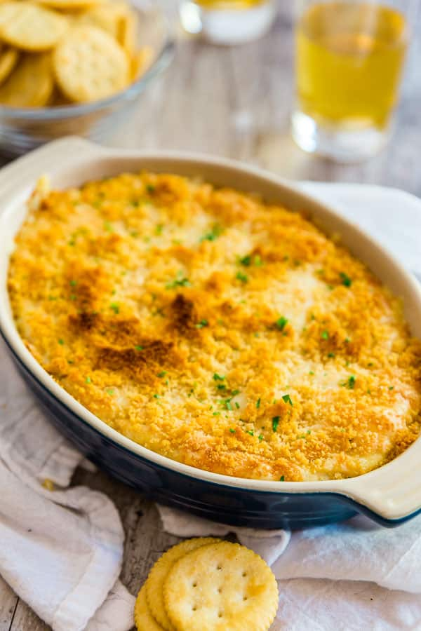 A pan of Hot Chicken Swiss Dipwith some beers and crackers around it,
