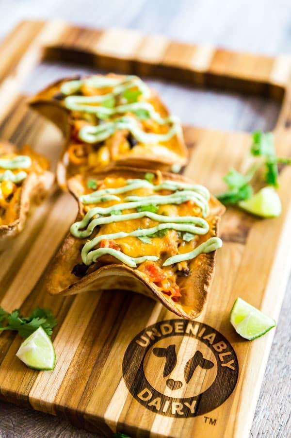 Cheesy Chicken Taco Bowls drizzled with avocado crema.