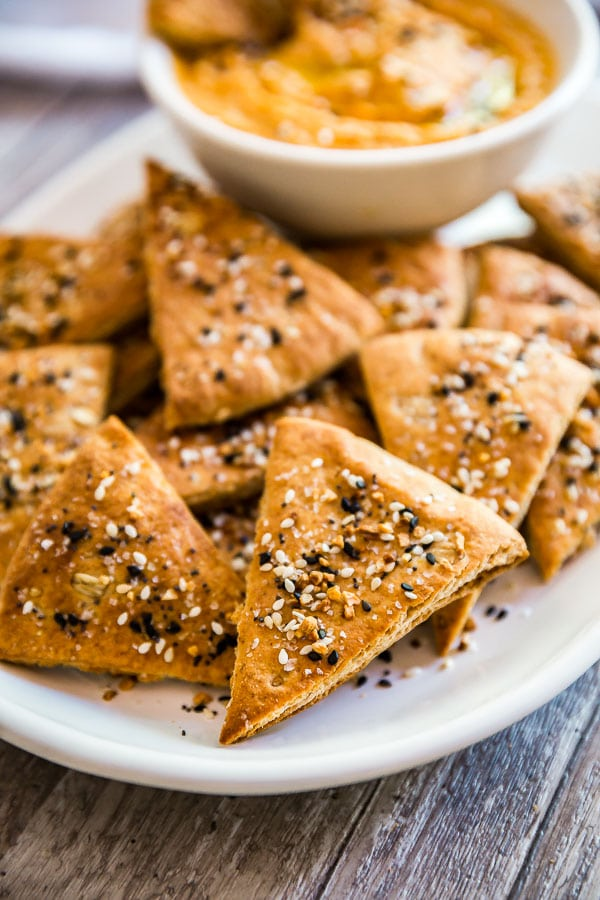 A close up shot of Everything Pita Chips with hummus i nthe back.