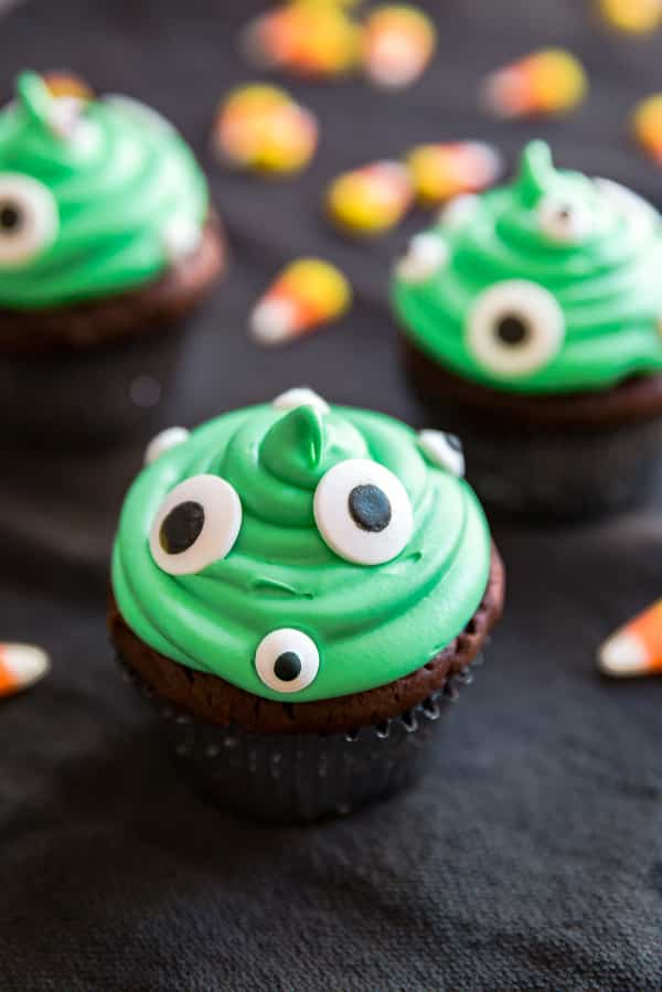 A close up image of a Monster Peanut Butter Cup Stuffed Cupcake with others behind it.