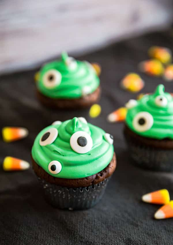 Monster Peanut Butter Cup Stuffed Cupcakes on a black cloth surrounded by candy corn.