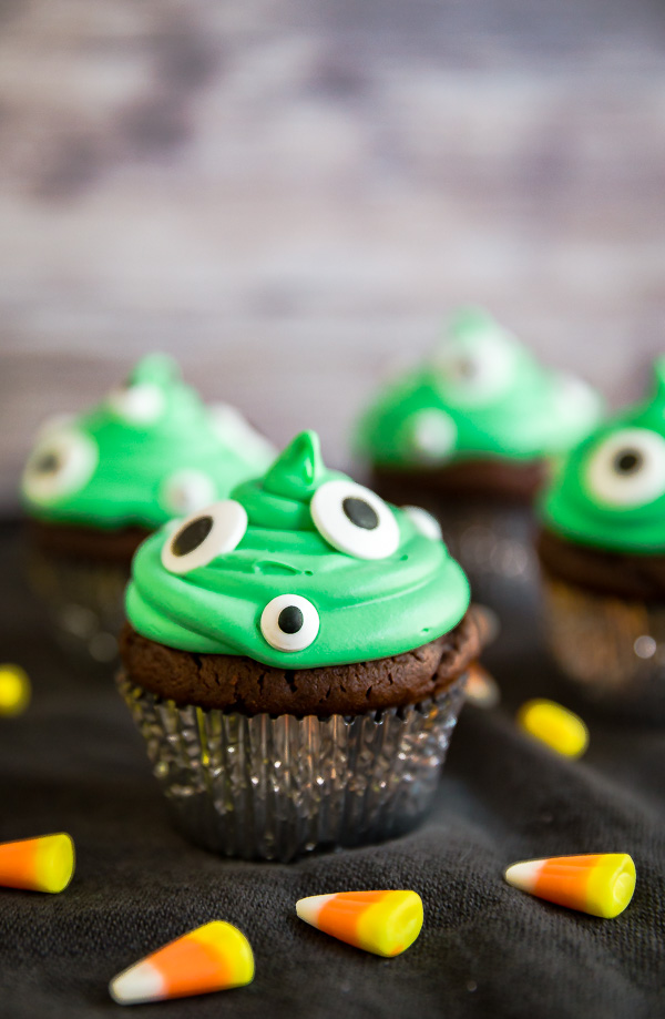 A Monster Peanut Butter Cup Stuffed Cupcakes with other cupcakes around it and candy corn as well.