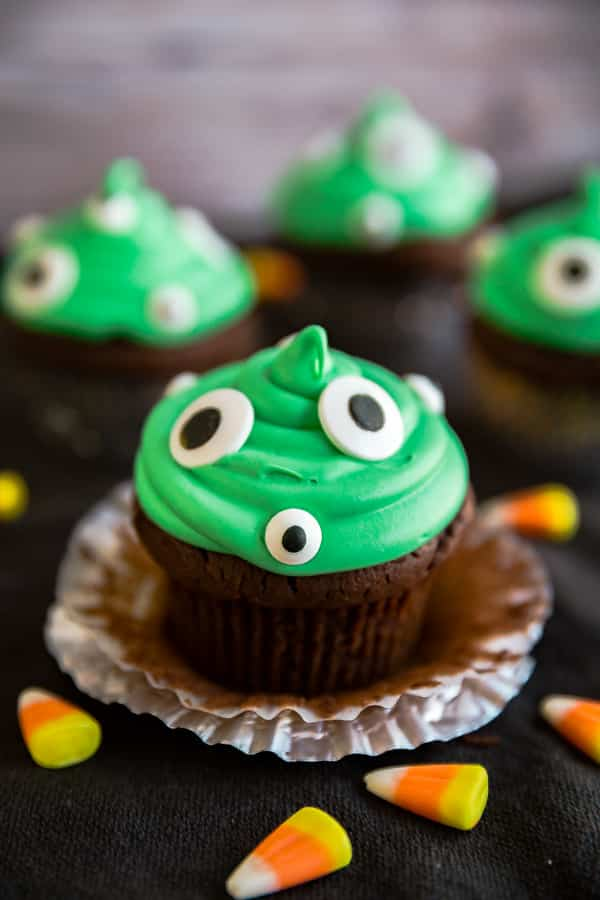 An image of Monster Peanut Butter Cup Stuffed Cupcakes and the front one has the cupcake liner peeled off it.