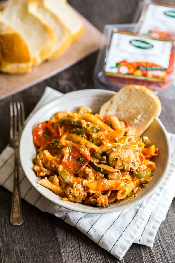 A bowl of Supreme Pizza One Pot Pasta with a piece of bread in it.