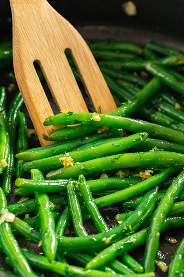 A close up side angle shot of string beans in a pan with a wooden spoon